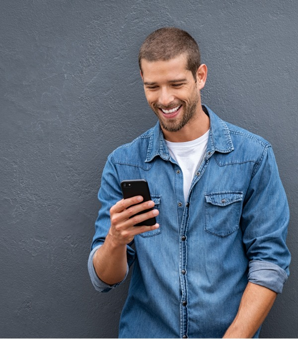 Cool, casual and smiling man looking down at his smartphone as he leans back against a wall. He's excited to find out about Ent Extras Checking.