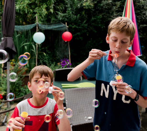 two  young boys blowing bubbles