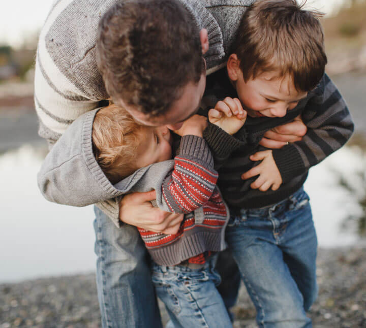 image of father hugging two young sons