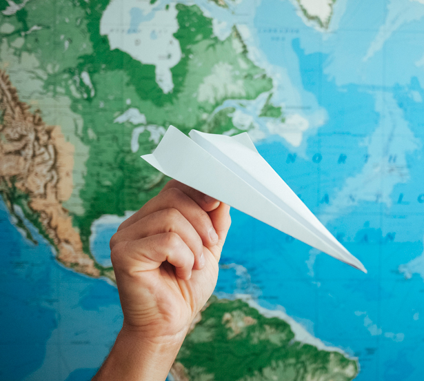 image of a hand holding paper airplane with map in the background
