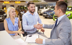 Couple car shopping and shaking hands with a salesman.
