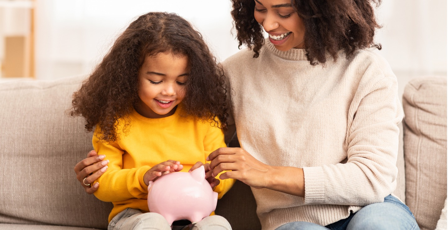 Family Savings. Cheerful Afro Mother Teaching Little Daughter How To Save Money Holding Piggybank Sitting On Sofa At Home