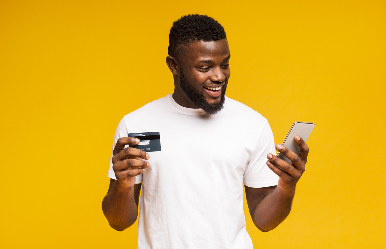 Online payment. Cheerful black man using credit card and smartphone for purchasing goods