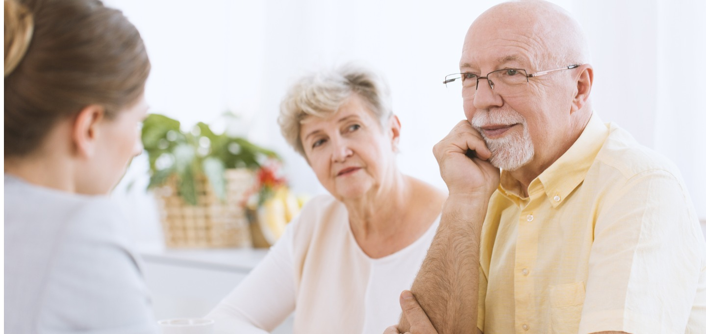 Senior couple at the meeting with insurance agent listening to an offer.
