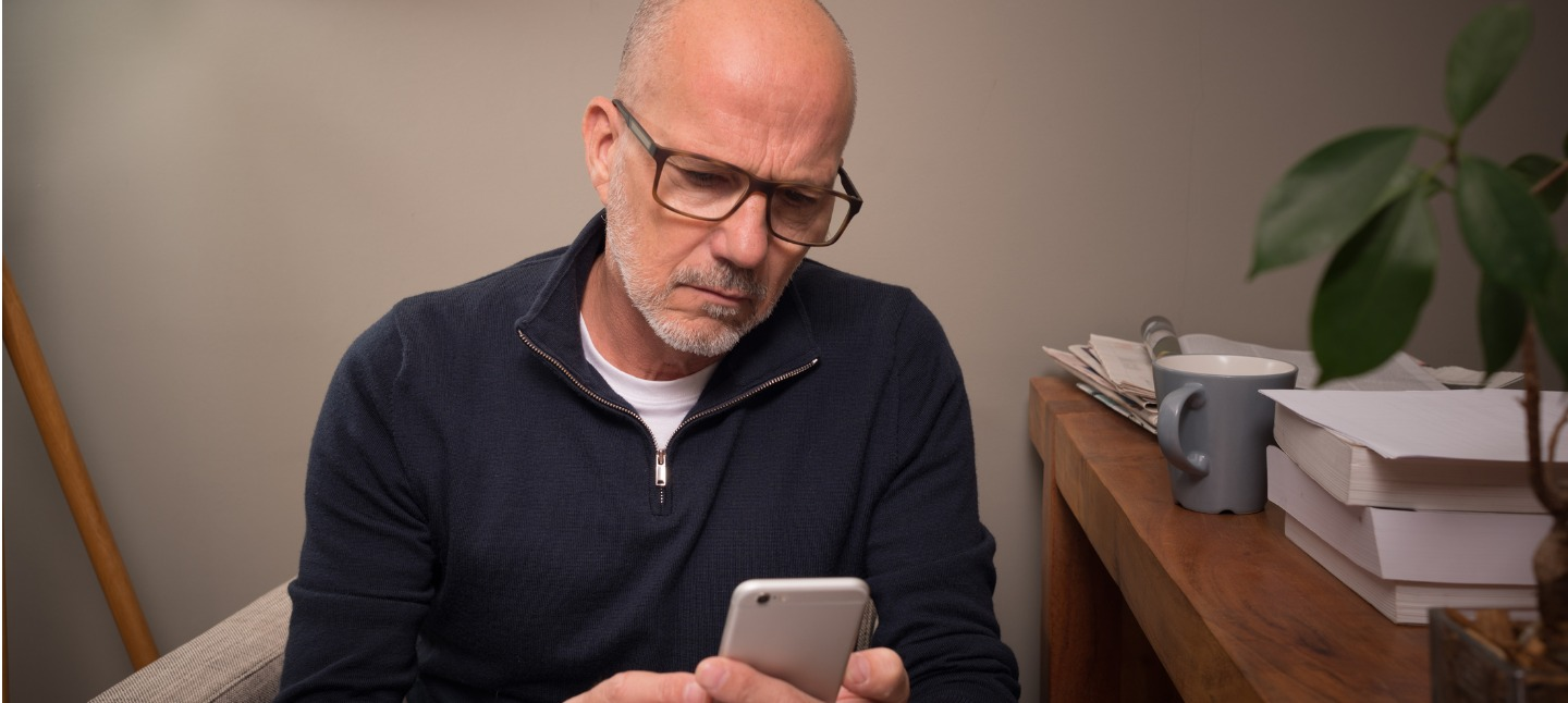 Mature man at home using smartphone for online banking, shopping, social media, e-mail, etc. The serious expression indicates there's something to think about ... phishing, e-mail scam, online abuse, identity theft, who knows what?
