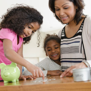 A woman with two young kids counting coins on a counter top with a small green piggy bank and a gray tin beside them.