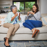 Two women sit on a neutral colored couch, sipping coffee and sharing tips.