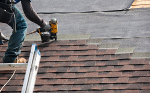 A worker on a roof, with a ladder, nailing shingles to tar paper.
